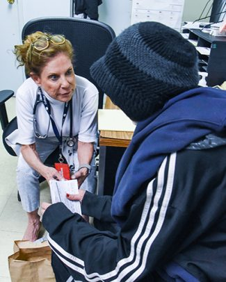 Clinical assistant professor Karen Cotler consults with a patient at a primary care clinic run by the UIC Community Outreach Intervention Projects in 2019. She is leading a new program to train newly-graduated nurse practitioners to work with patients with opioid use disorders at that clinic and sites like it.