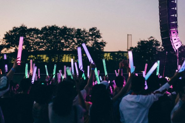 Crowd of concertgoers with light sticks.
