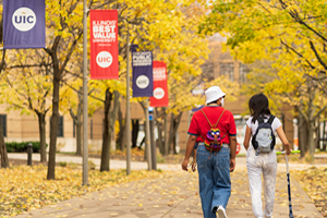 Students walking on campus viewing fall foliage